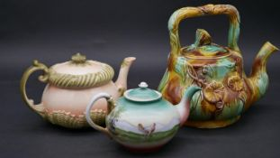 A collection of three antique teapots. Two majolica tea pots, one with sea shells and one with