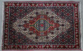 A Persian rug with triple lozenge medallions on stylised floral ground and borders. L.114 W.73cm