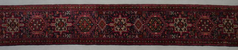 A Kazak runner with repeating hooked medallions on a midnight ground contained within stylised
