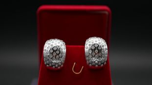 A red velvet boxed pair of half hoop white metal (tested 18 carat white gold) and diamond pierced