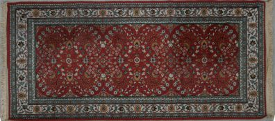 A Persian style rug with repeating petal motifs across a burgundy field contained within