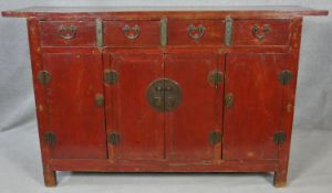 A Chinese lacquered and brass bound sideboard with four frieze drawers above four panel doors on