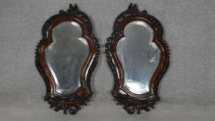 A pair of C.1900 pier mirrors with shaped bevelled plates in foliate carved mahogany frames. H.63.