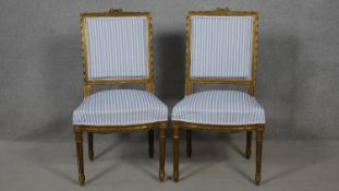 A pair of 19th century Louis XVI style carved giltwood dining chairs in striped upholstery on fluted
