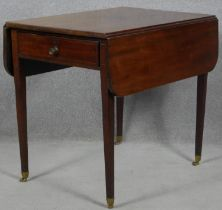 A Georgian mahogany drop flap Pembroke table fitted with a pair of end drawers raised on square