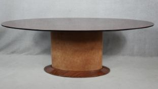 A contemporary oval dining table on maple pedestal base. H.76 L.220 W.120cm