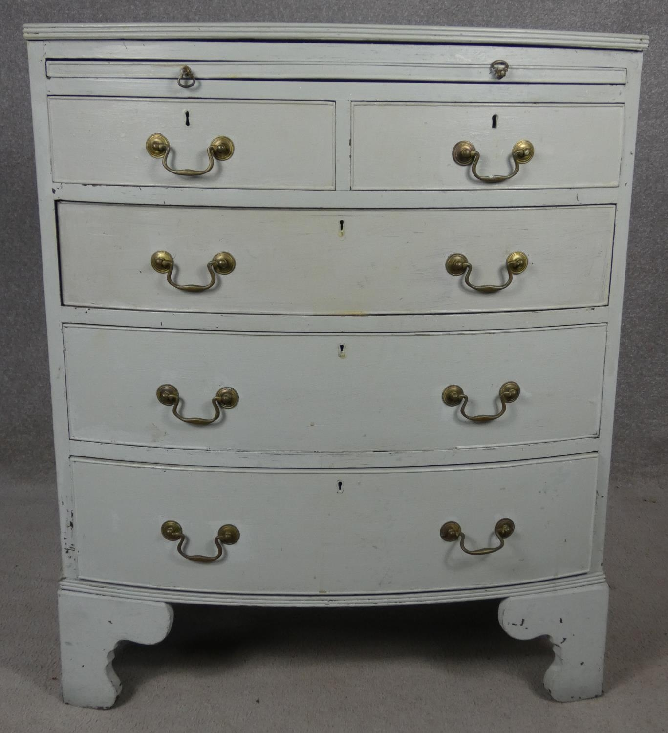 A Georgian style white painted bowfronted chest of drawers with brushing slide and brass swan neck