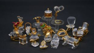 A collection of twenty Swaovski crystal memories with gilt metal details. To include flower pots,
