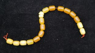 A string of seventeen antique amber prayer beads. (one cracked) L.24cm