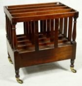 A 19th century style mahogany Canterbury fitted with magazine sections and a base drawer on turned