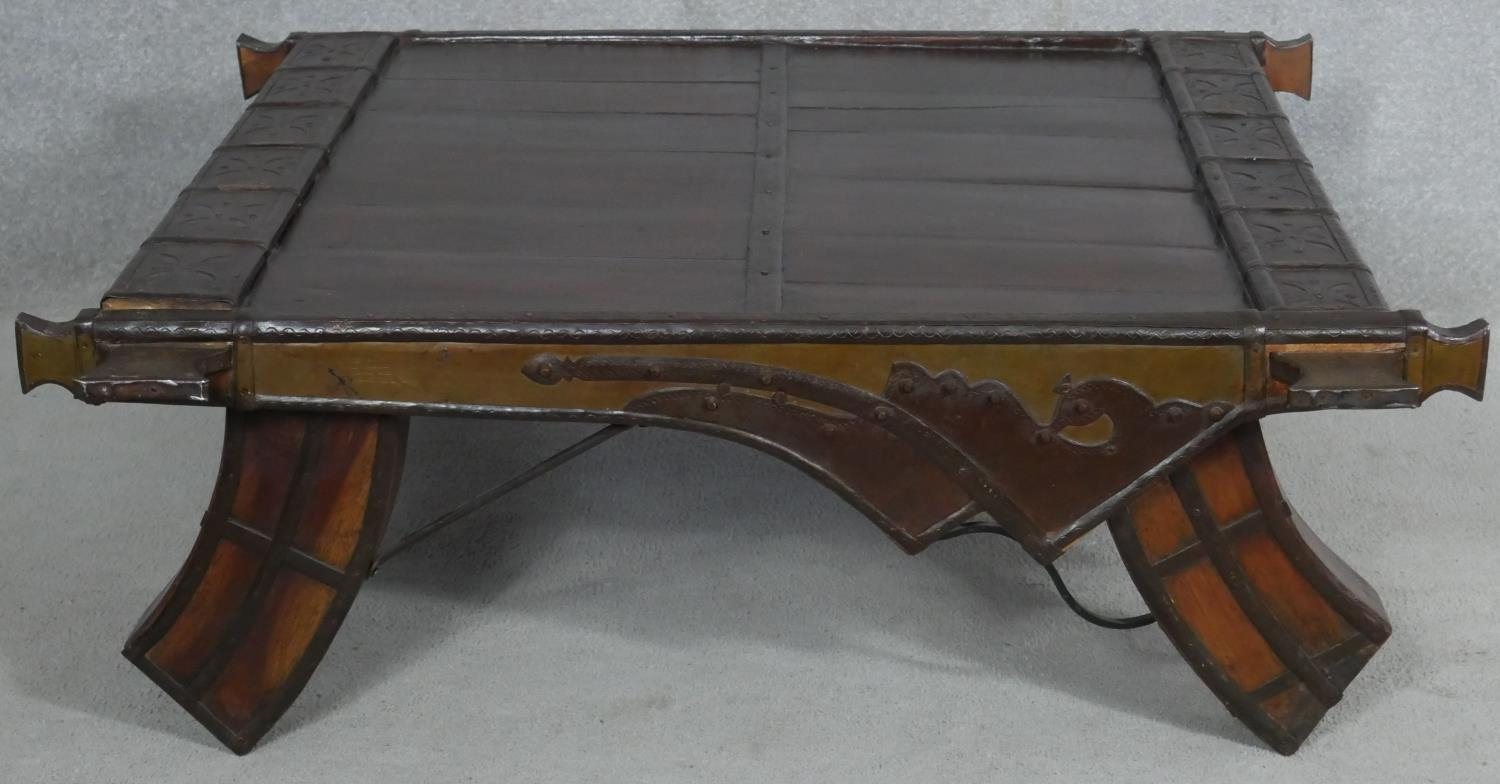 An Eastern hardwood metal bound coffee table on shaped swept supports. H.36 L.103 W.98cm