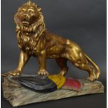 A gold and polychrome glazed ceramic sculpture of a lion roaring and standing on the Belgian flag on