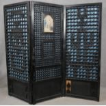 A Chinese style ebonised three panel room divider with central panel inset with glazed watercolour