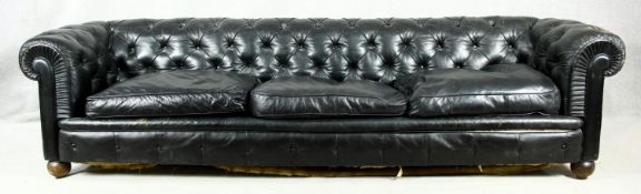 A three seater Chesterfield sofa in deep buttoned leather upholstery on bun feet. H.70 W.275 D.90cm