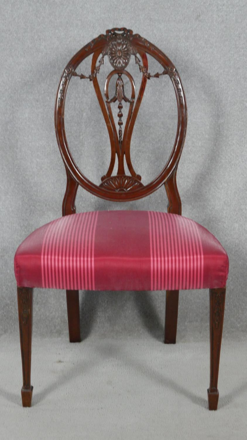 A 19th century mahogany dining chair with carved swag and ribbon detail to the back raised on square