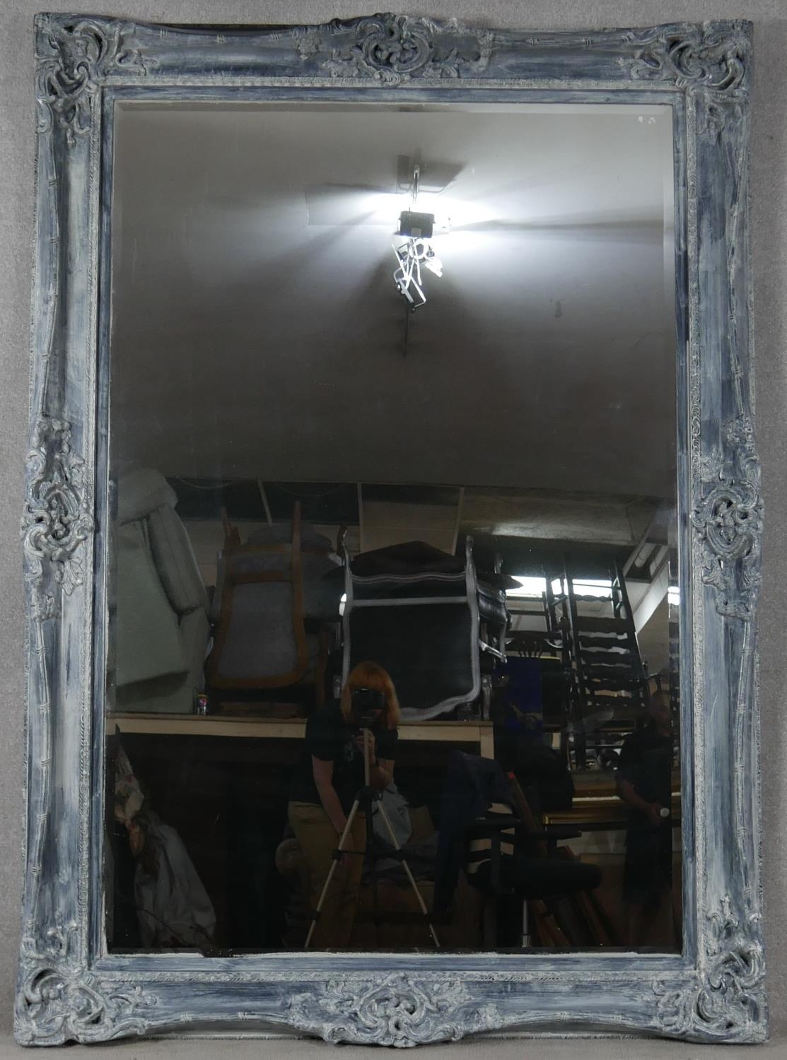 A large wall mirror with bevelled plate in distressed Rococo style frame. H.216 W.154cm