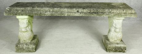 A weathered reconstituted stone garden bench on twin supports. H.46 W.128 D.38cm