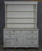 A late 19th century distressed painted pine kitchen dresser with upper open plate rack above base