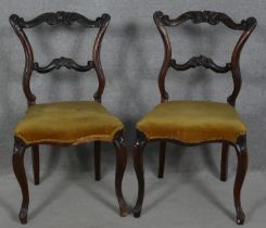 A pair of late 19th century mahogany dining chairs with carved and shaped back rails on cabriole
