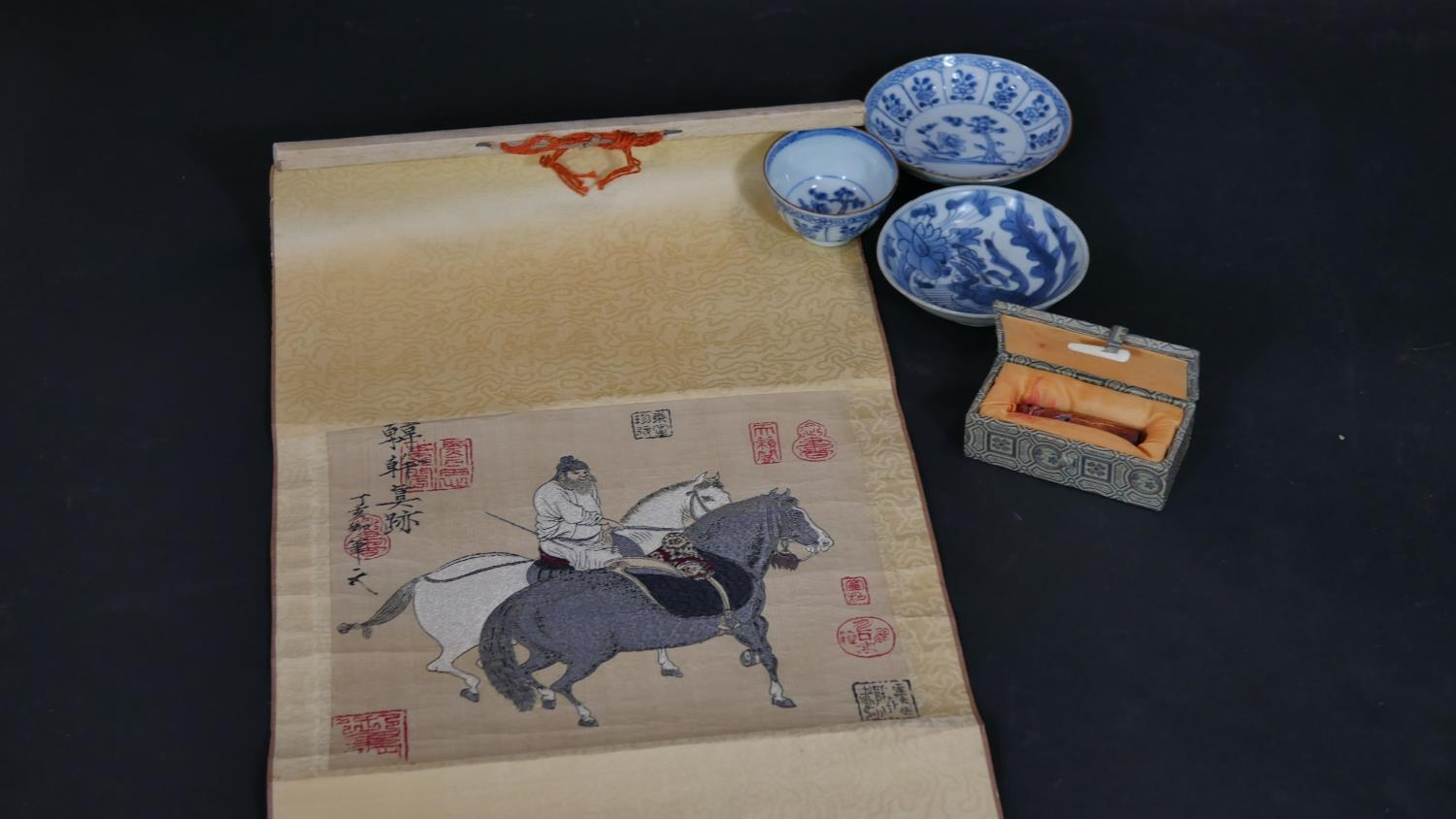 A Chinese embroidered scroll, three items of hand painted blue and white ceramics and a cased carved
