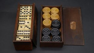 A 19th century boxed set of bone and ebony dominos with a set of boxwood draughts in a wooden box