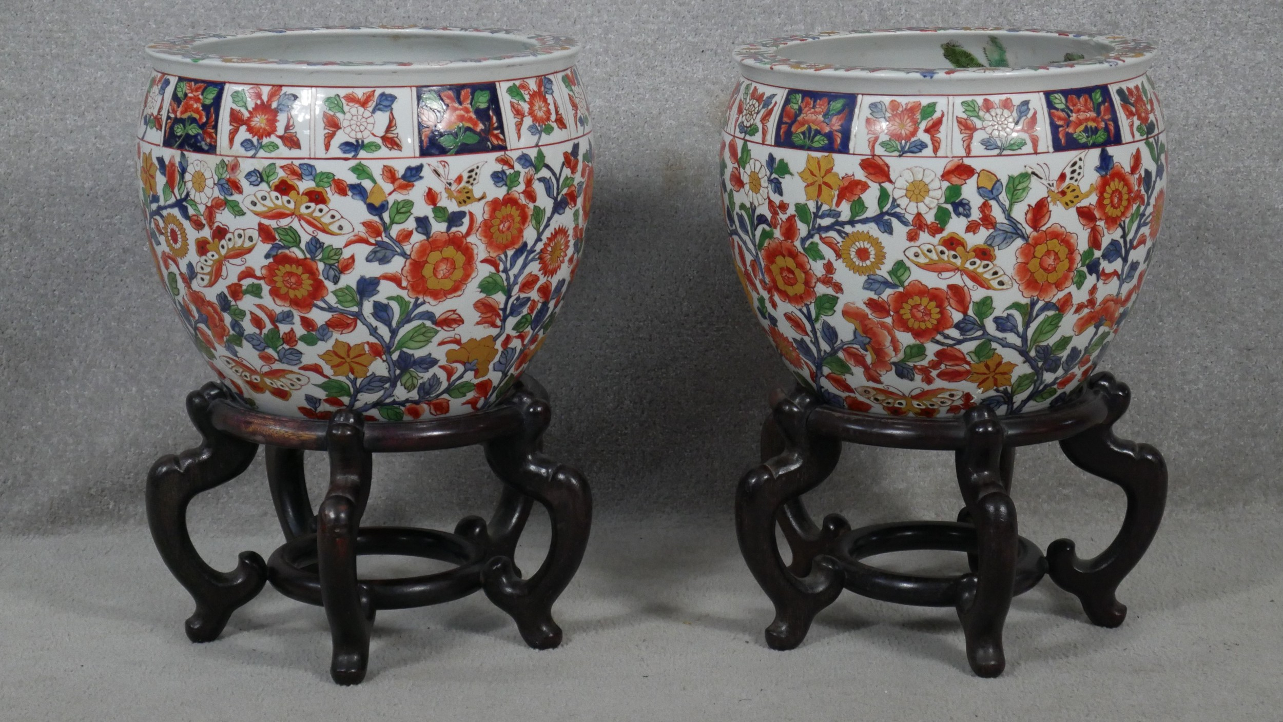 A pair of early 20th century glazed Chinese Imari ceramic planters/fish bowls on carved hardwood