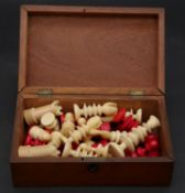 A 19th century complete carved ivory chess set, one set stained red, with engraved detaling in a