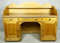 A 19th century pitch pine desk with shaped galleried back above inset leather top over pedestal
