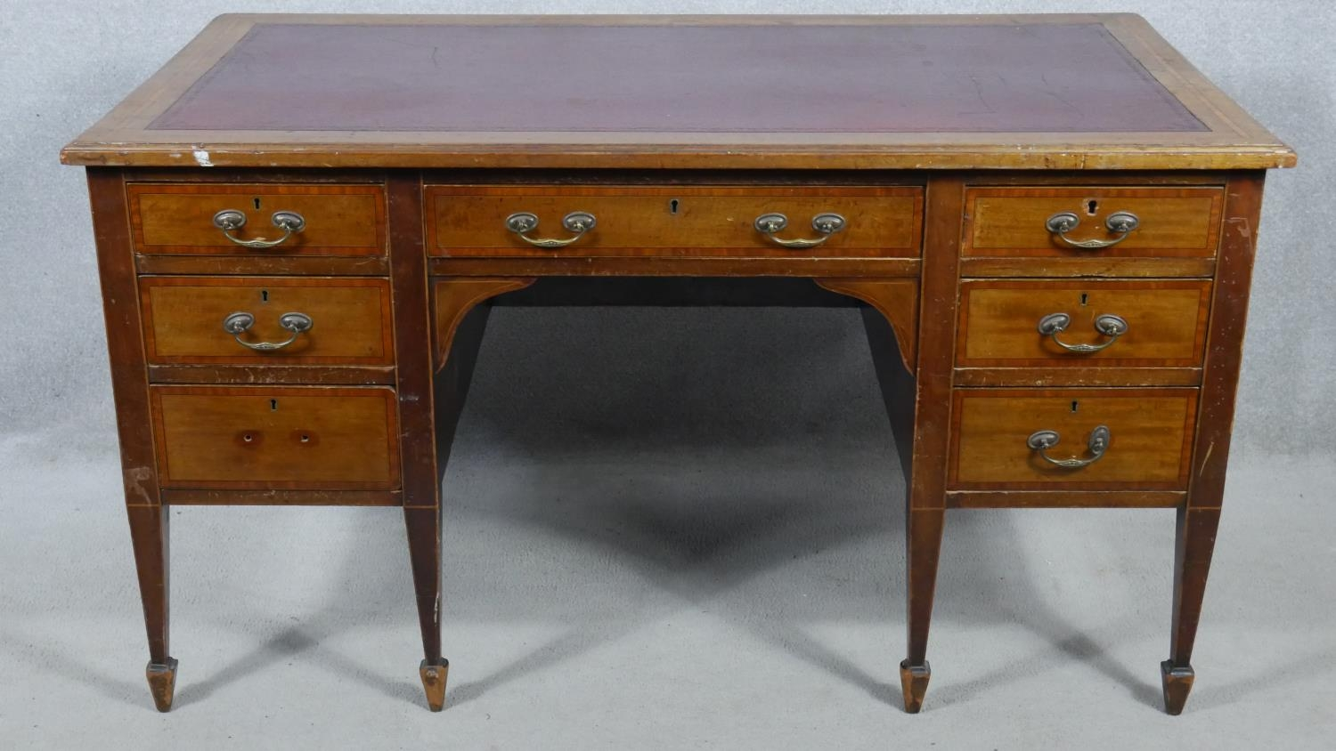An Edwardian mahogany and crossbanded kneehole desk with inset leather top raised on square tapering