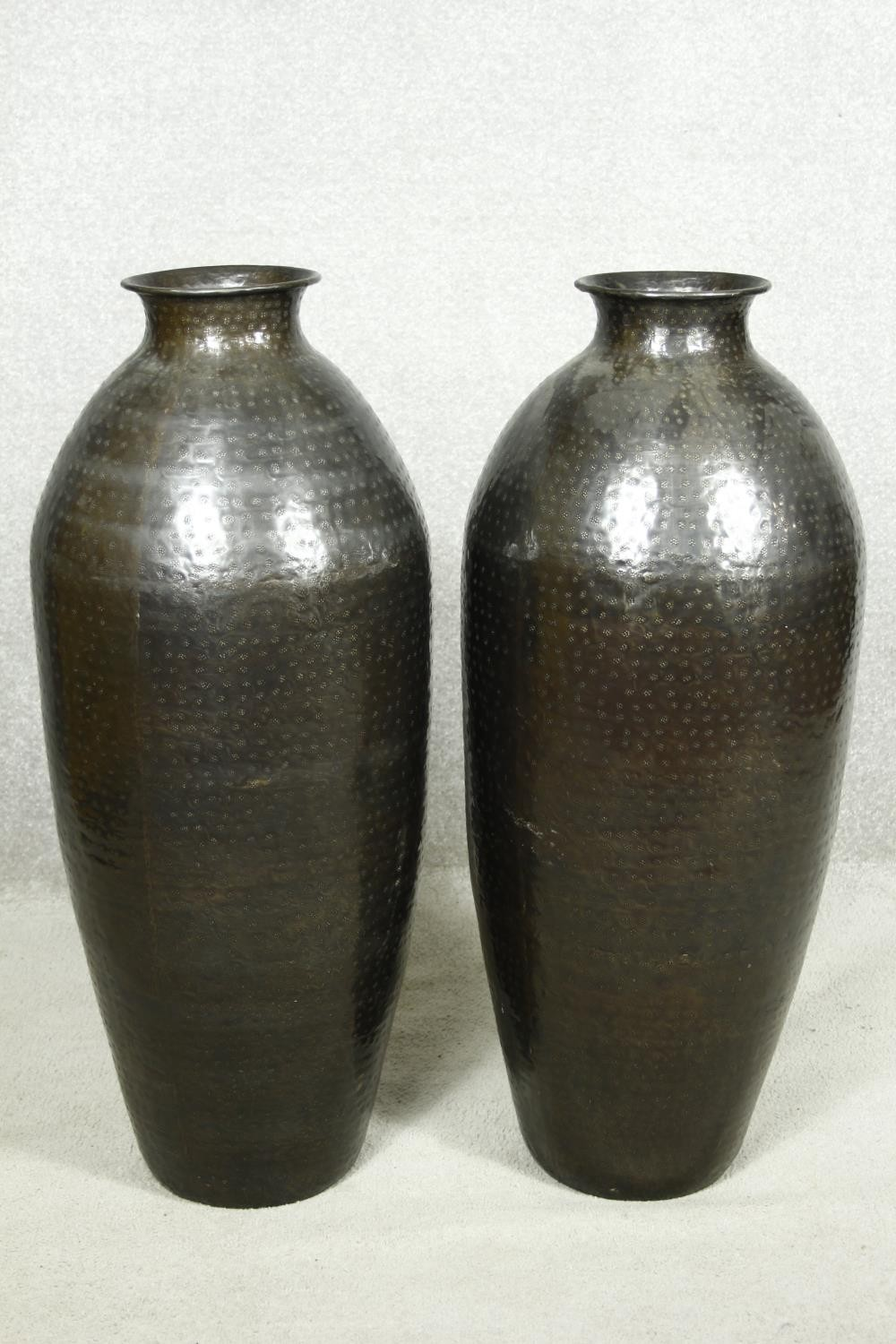 A pair of large contemporary floor standing hammered brass vases. H.79cm
