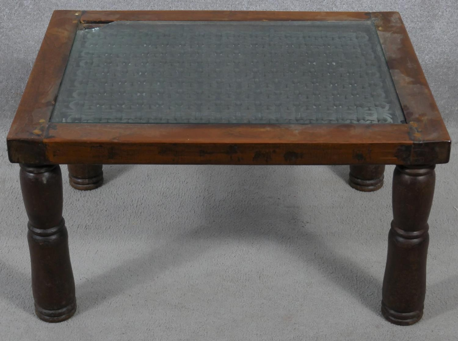 An Indian hardwood occasional table with plate glass on a metal lattice work inset top. H.38 L.68.