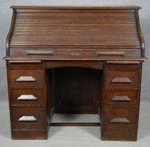 A late 19th century oak roll top desk with tambour shutter revealing fitted interior on twin