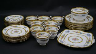 A Paragon porcelain tea service with floral decoration, yellow scalloped rim and gilt highlights