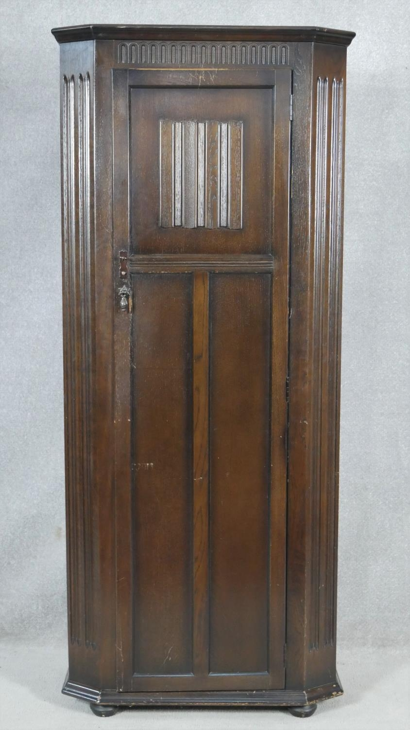 A mid century oak Jacobean style floor standing hall cupboard with carved linenfold panel door on