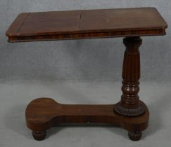 A William IV mahogany bed table with rise and fall action and a pair of adjustable reading slopes