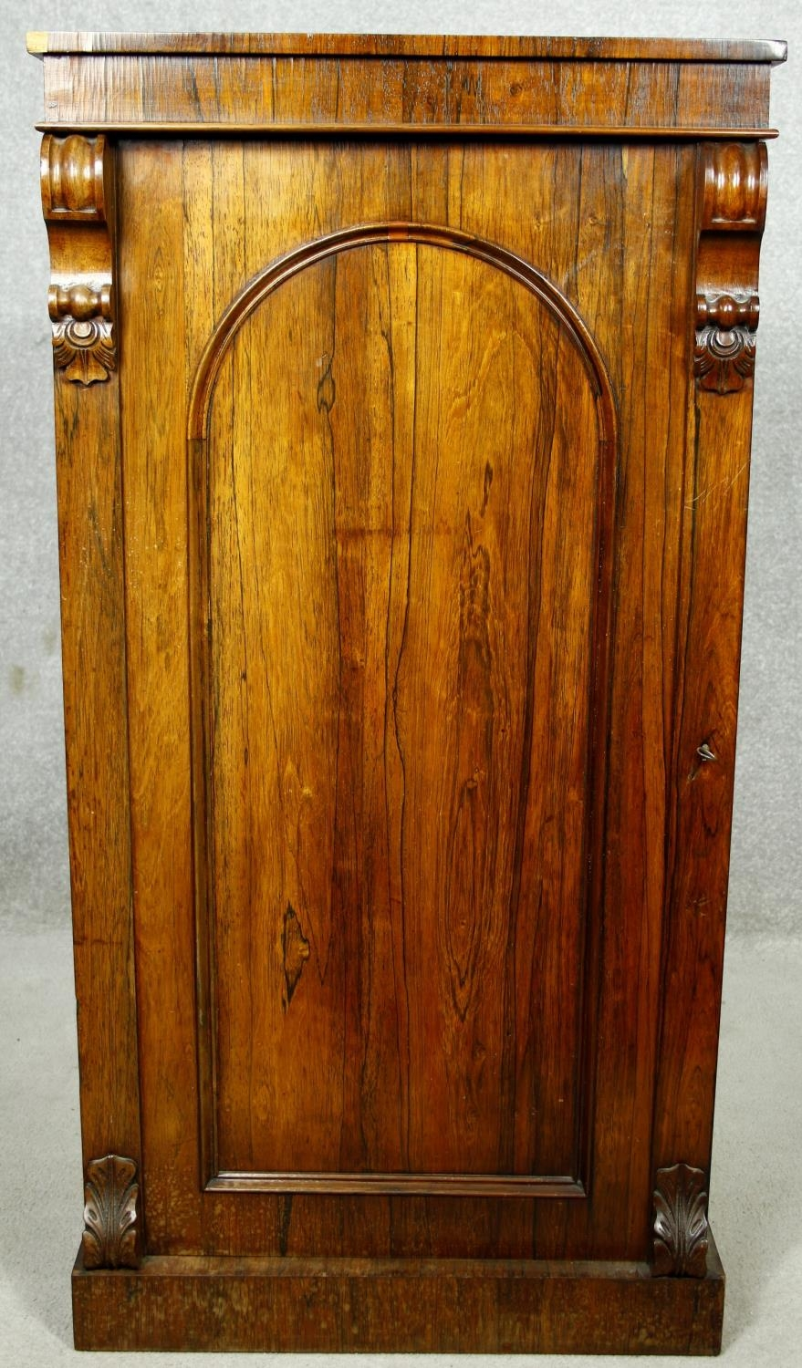 An early Victorian rosewood pier cabinet with arched panel door enclosing shelves on plinth base.