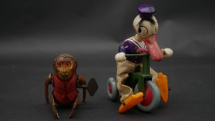 Two vintage wind up tin plate toys; a 1930's Japanese Paradise celluloid wind up tricycle Donald