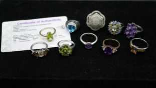 Ten gemset rings, one with certificate. To include a 9ct yellow gold peridot ring, amethyst ring,