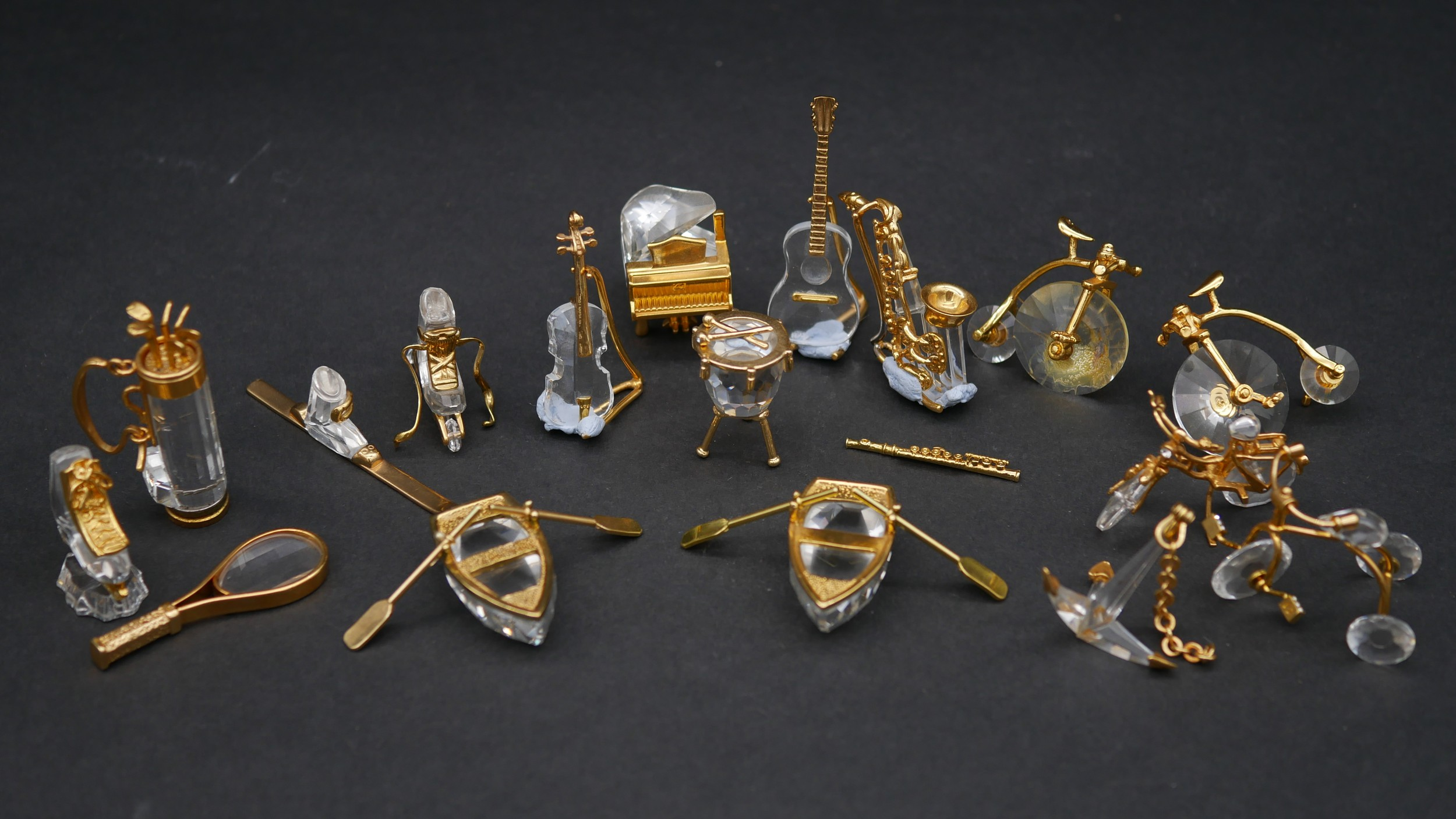 A collection of eighteen Swarovski crystal memories with gilt mounts; a pair of rowing boats with