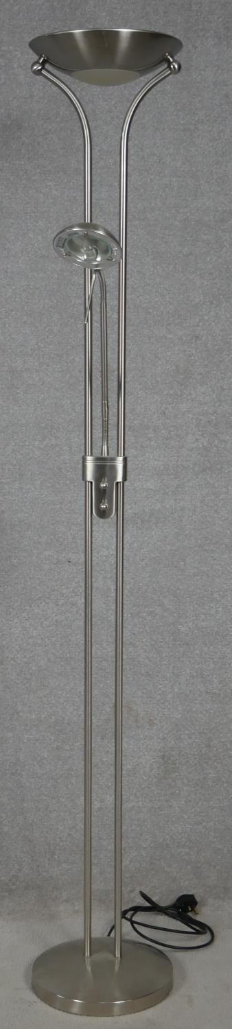 A contemporary chrome standing uplighter with adjustable reading lamp arm. H.182cm