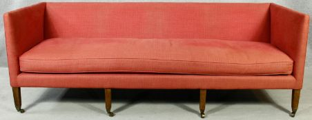 A Georgian style sofa upholstered in calico raised on eight square tapering supports terminating