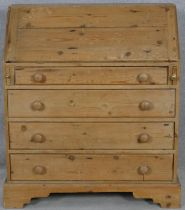 A 19th century pine bureau with fall front revealing a fitted interior above four long graduated