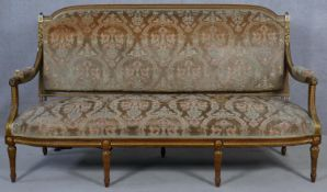 A carved and giltwood Louis XVI style canape in cut floral upholstery raised on fluted turned