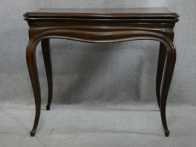 An antique mahogany Louis XV style fold over top card table with tooled leather inset top and pull