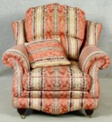 A contemporary upholstered armchair on turned supports terminating in brass cup casters. H.100 W.100