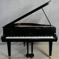 A Yamaha G1 grand piano in black gloss lacquered case on brass roller castors, serial number 2083203