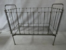 A Victorian wrought iron child's cot with fall front panel. H.114 L.124 W.63cm