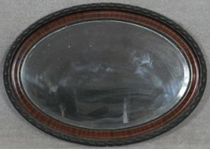 An early 20th century oval wall mirror with bevelled plate. H.61.5 W.86cm