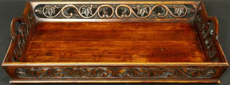An Eastern hardwood twin handled tray with carved and pierced floral gallery. L.70 W.46cm