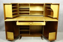 A mid century vintage teak Newcraft & Co. office in a box, fitted cabinet with doors opening to